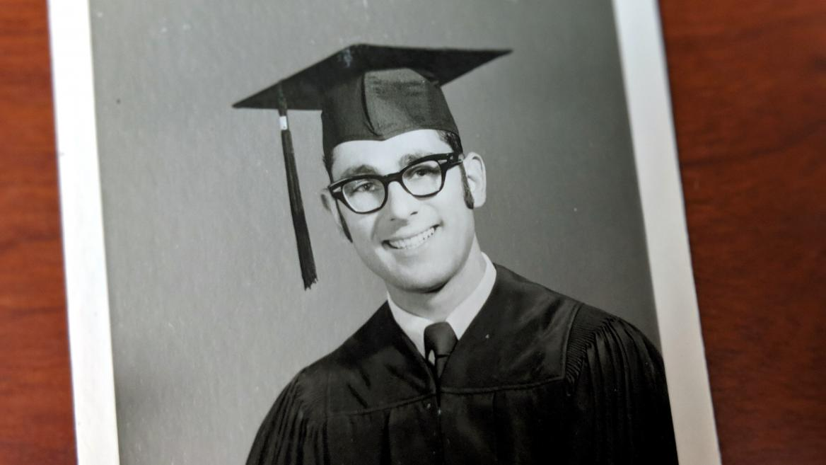 Geoffrey Gonsher graduation photo from 50 yrs ago, wearing black cap and gown and thick, black rimmed glasses