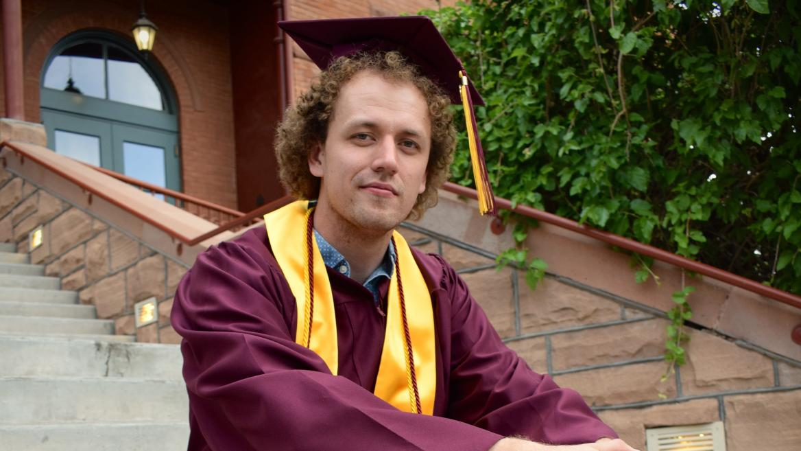Jimmy Arwood sits on the steps of Old Main in his grad cap and gown